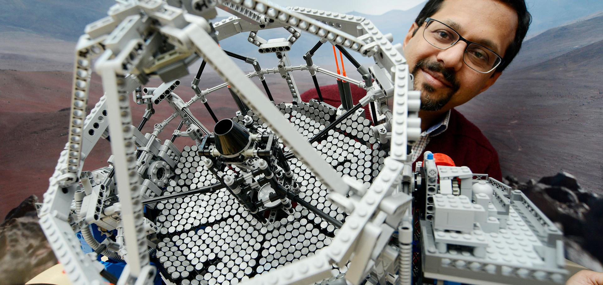 Man with Lego model of a telescope