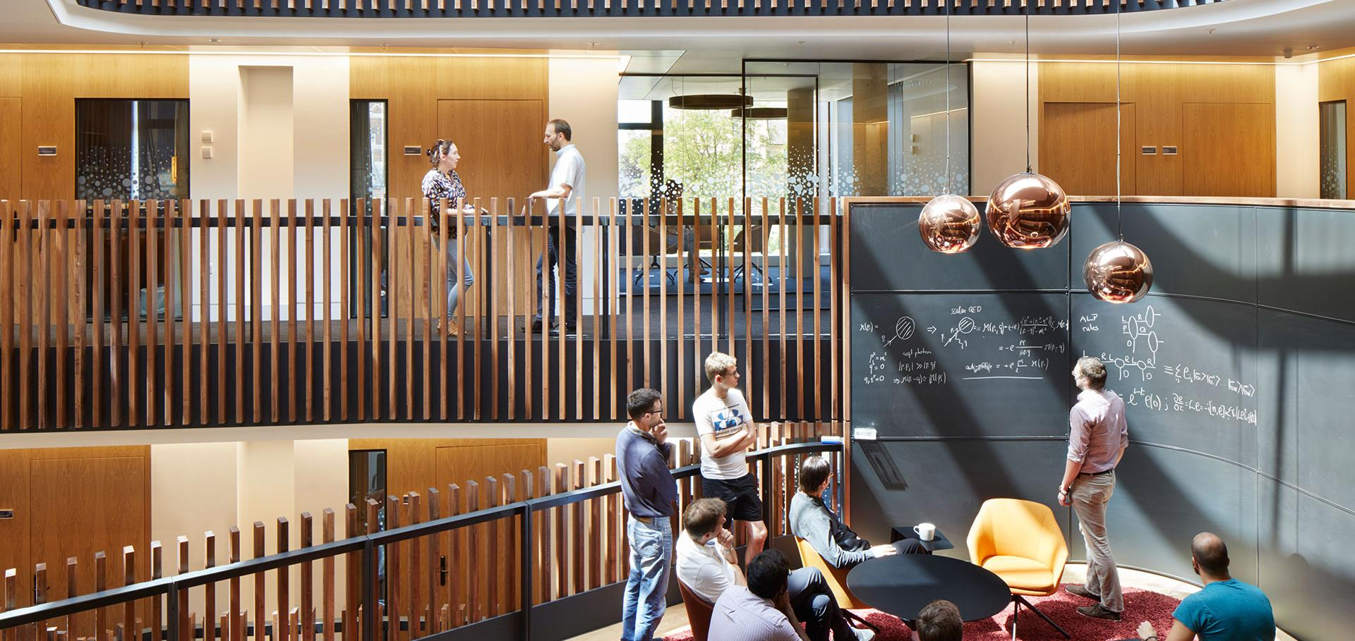 Theoretical physicists working at a blackboard collaboration pod in the Beecroft building.