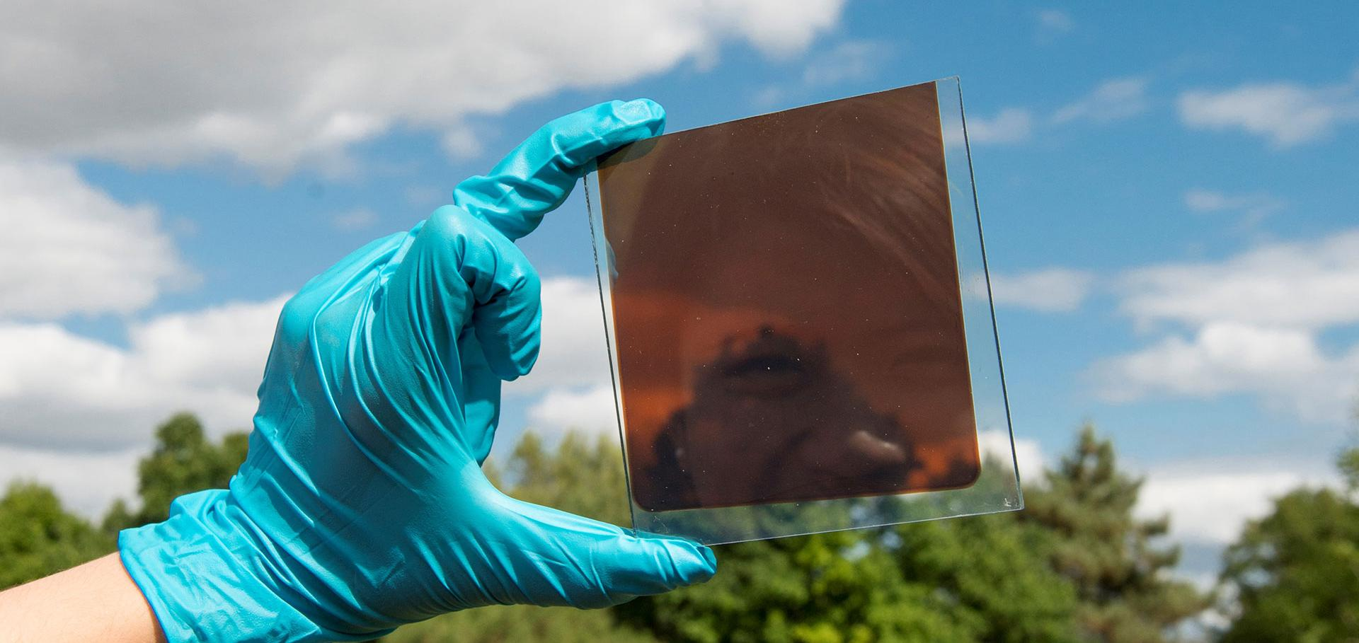 Reflection of smiling face in photovoltaic cell